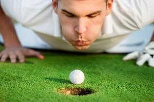 Играч на голф помага на топката чрез духане