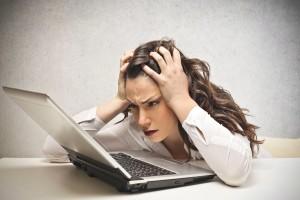 Стресирана жена гледа лаптопа